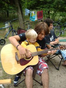 Alex teaching Isaac how to play the guitar.